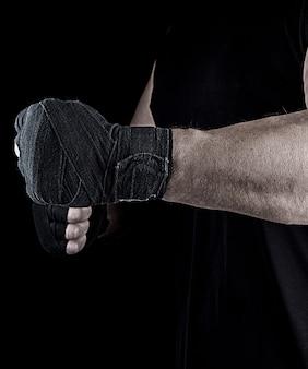 L'atleta è in piedi con un braccio allungato fasciato