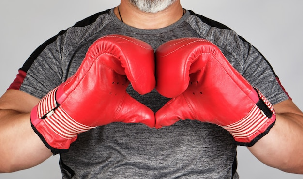 L'atleta in guanti di cuoio di pugilato rossi mostra le mani con un simbolo del cuore