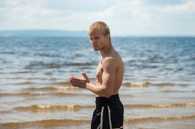 L'atleta si scalda prima di allenarsi contro il mare