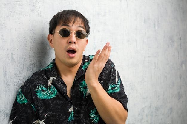 L'attrezzatura d'uso di estate del giovane uomo cinese ha sorpreso e colpito