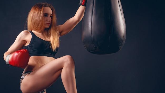 L'attrezzatura sportiva atletica della ragazza ha una mano che indossa un guantone da boxe, con spazio di testo libero