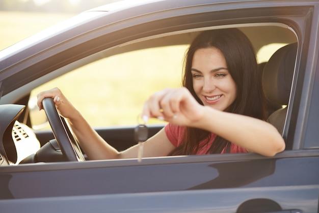 L'autista femminile felice tiene le chiavi dall'automobile