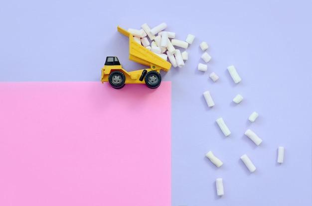 L'autocarro con cassone ribaltabile getta pezzi di marshmallow dalla sua schiena rialzata
