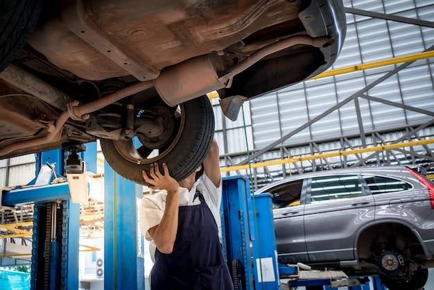 L'automobile cambiante del meccanico spinge dentro l'officina riparazioni automatica