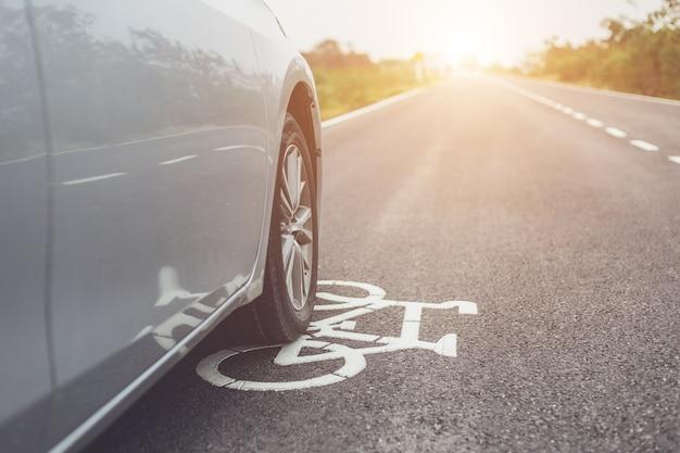 L'automobile moderna che funziona sulla strada asfaltata / pista ciclabile e calpesta sul segno bianco della bicicletta