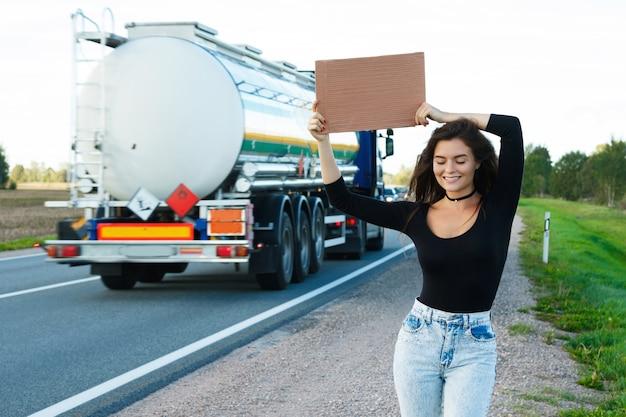 L'autostoppista sulla strada tiene in mano un cartello di cartone bianco