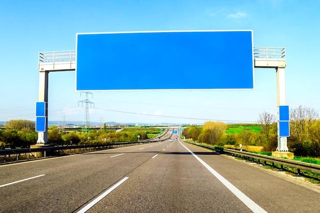 L'autostrada senza pedaggio blu in bianco firma sopra la strada il giorno soleggiato