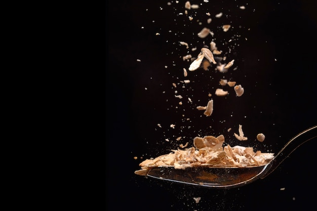 L'avena del primo piano si sfalda volando dei cereali che cade in un cucchiaio isolato
