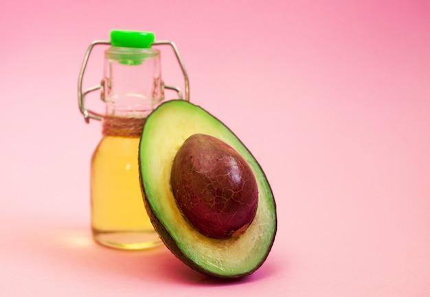 L'avocado e l'avocado lubrificano in bottiglia su fondo rosa.