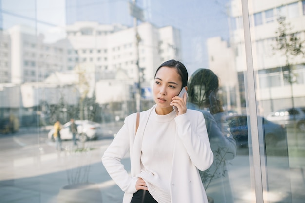 L'avvocato attraente donna asiatica adulta è in piedi vicino a un centro di ufficio che ha una conversazione spiacevole con il suo capo o cliente al telefono