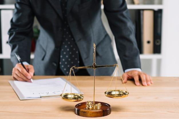 L'avvocato firma il documento di contratto davanti alla scala della giustizia sopra la tavola
