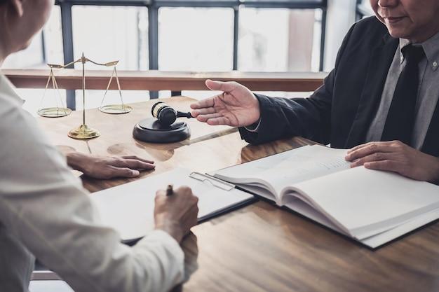 L'avvocato o il giudice maschio si consultano con un gruppo di lavoro che si occupa di clienti, servizi legali e legali