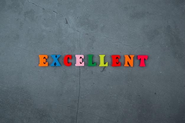 L'eccellente parola multicolore è composta da lettere di legno su una parete grigia intonacata