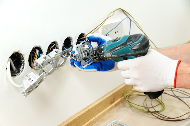L'elettricista installa la presa elettrica usando un cacciavite