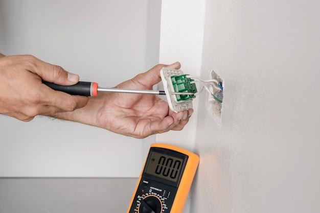 L'elettricista sta usando un cacciavite per fissare il cavo di alimentazione alla presa a muro.