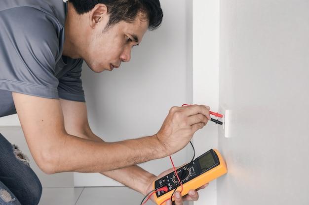 L'elettricista sta usando un misuratore digitale per misurare la tensione alla presa di corrente