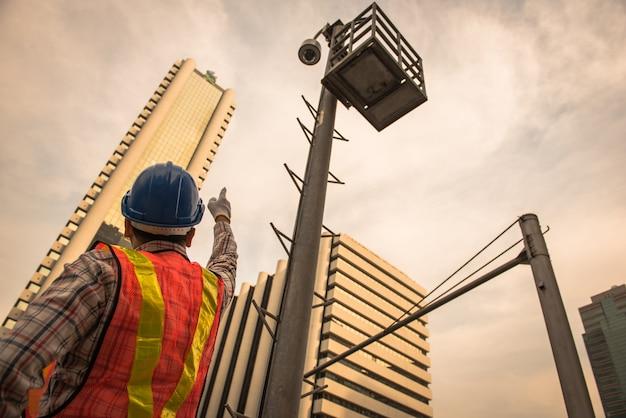 L'elettricista verifica le installazioni elettriche e i cavi della macchina fotografica a circuito chiuso sul palo di recinzione all'aperto.