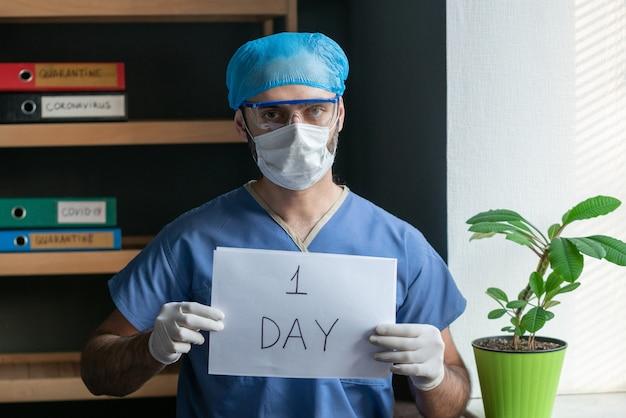 L'erba medica maschio tiene un foglio di carta con l'iscrizione un giorno.