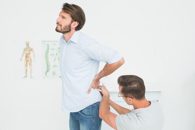 L'esame maschio del fisioterapista equipaggia indietro