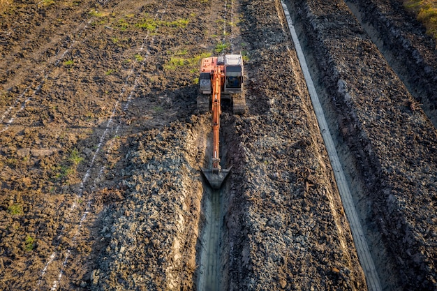 L'escavatore a cucchiaia rovescia di vista dell'angolo alto sta colpendo il giardino della scanalatura e l'area agricola tailandia