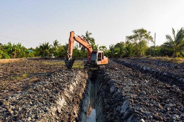 L'escavatore a cucchiaia rovescia sta colpendo il giardino della scanalatura e l'area agricola tailandia