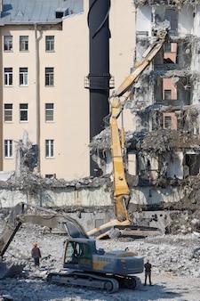 L'escavatore-distruttore si ribalta durante la demolizione di edifici