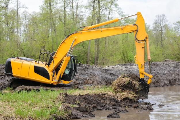 L'escavatore raccoglie una grande quantità di terreno per il canale del sistema di irrigazione delle costruzioni in campagna per l'irrigazione