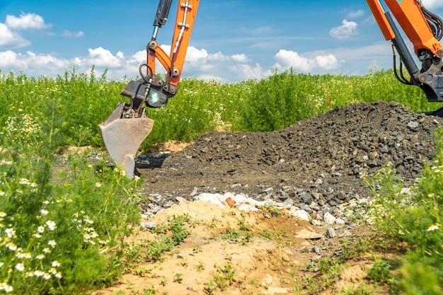 L'escavatore scava ghiaia per la costruzione di strade