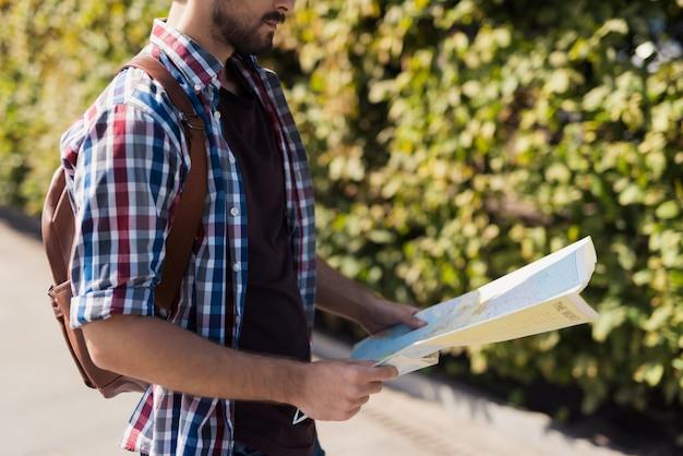 L'escursionista solitario sta studiando una mappa pianificando un percorso.