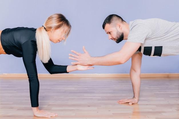 L'esecuzione attraente degli atleti della donna e dell'uomo si siede su sulla stuoia di yoga. fare esercizio fisico, definizione del muscolo dello stomaco. lavorare in coppia. belle giovani coppie atletiche sportive che fanno insieme gli esercizi.