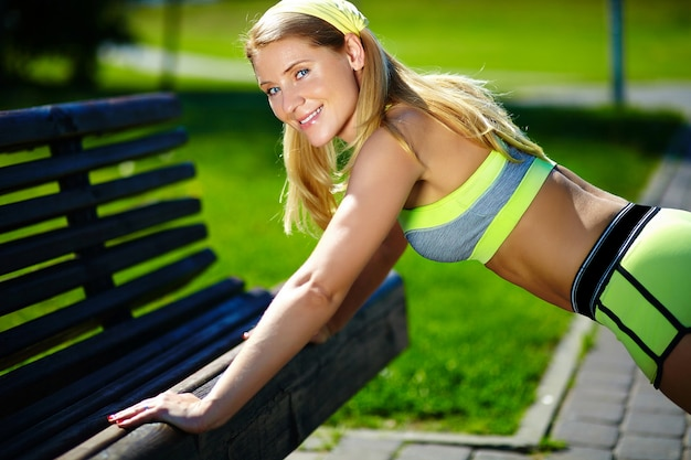 L'esercizio che fa la donna spinge aumenta nel sorridere all'aperto della donna di forma fisica di sport di addestramento di allenamento allegro e felice