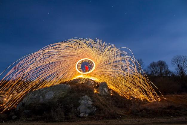 L'esposizione lunga ha sparato dell'uomo che sta sulla collina rocciosa che fila la lana d'acciaio nel cerchio che fa le docce del fuoco d'artificio delle scintille d'ardore gialle luminose sul fondo blu del cielo notturno. concetto di arte della pittura leggera.