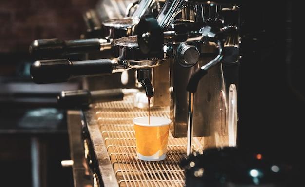 L'espresso ha sparato dalla macchina per il caffè in caffetteria, caffettiera in caffetteria