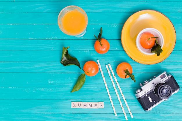 L'estate ha messo con i mandarini e succo e macchina fotografica su superficie di legno