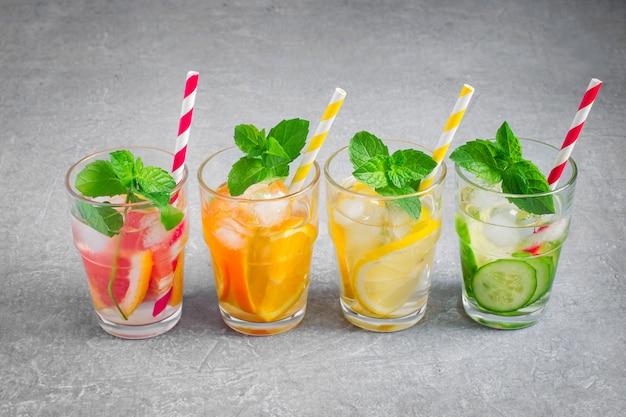 L'estate rinfrescante beve l'acqua con ghiaccio e limone, arancia, pompelmo e cetriolo