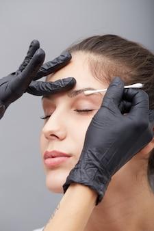 L'estetista applica il trucco permanente sulle sopracciglia