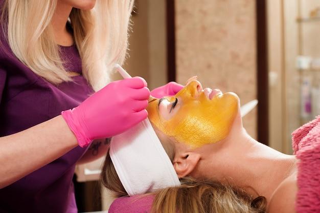 L'estetista applica una maschera d'oro sul viso di una donna