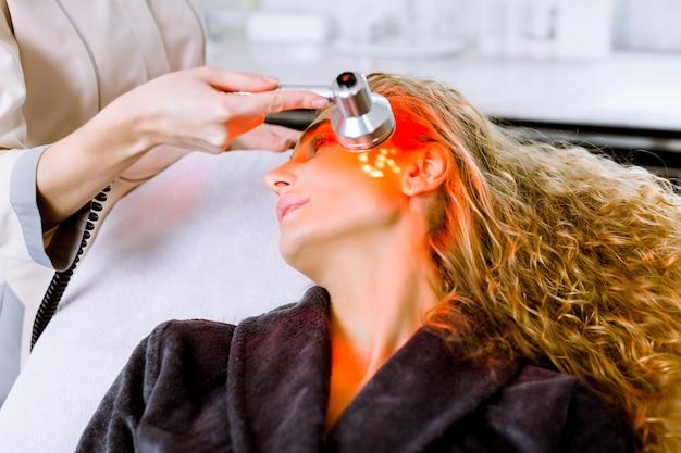 L'estetista che fa la terapia della luce principale rossa alla donna bionda nel salone di bellezza, terapia fotografica facciale per la pulizia dei pori della pelle. trattamenti anti-invecchiamento e foto ringiovanimento, da vicino