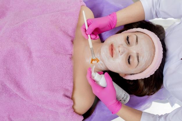 L'estetista crea una maschera viso all'argilla contro l'acne sul viso di una donna per ringiovanire la pelle. trattamento cosmetologico della pelle problematica su viso e corpo.