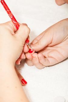 L'estetista decora con i fiori le unghie delle mani del cliente