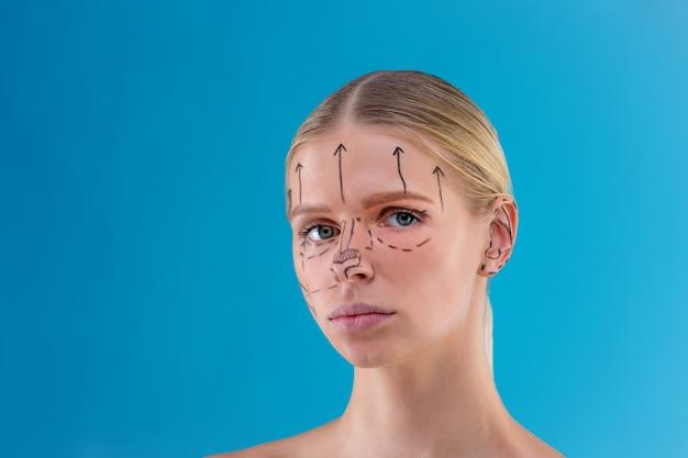 L'estetista disegna le linee di correzione sul viso della donna. prima dell'operazione di chirurgia plastica. isolato su blu