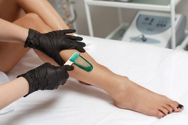 L'estetista fa la depilazione della giovane donna sulla sua gamba con la cera