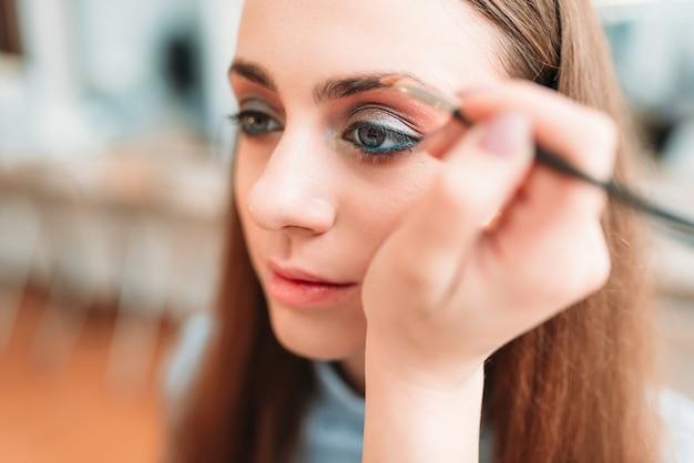 L'estetista professionista lavora con le sopracciglia della donna nello studio di bellezza.