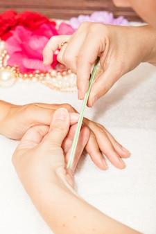 L'estetista pulisce le unghie del cliente prima di applicare lo smalto