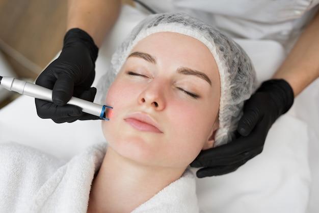 L'estetista terapista esegue un trattamento laser sul viso di una giovane donna presso la clinica beauty spa
