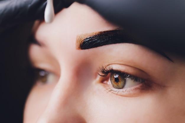 L'estetista-truccatrice applica l'henné di vernice su sopracciglia strappate, progettate, tagliate in un salone di bellezza nella correzione della sessione. cura professionale per il viso.