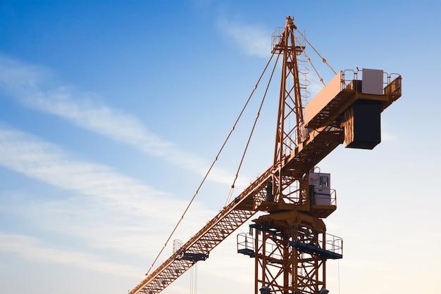 L'estratto industriale con costruzione cranes le siluette sopra il cielo stupefacente del tramonto