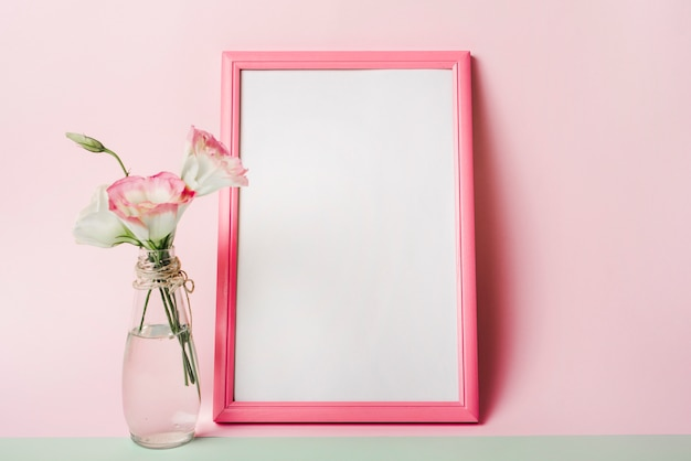 L'eustoma fiorisce in vaso vicino alla struttura bianca in bianco con il confine contro fondo rosa