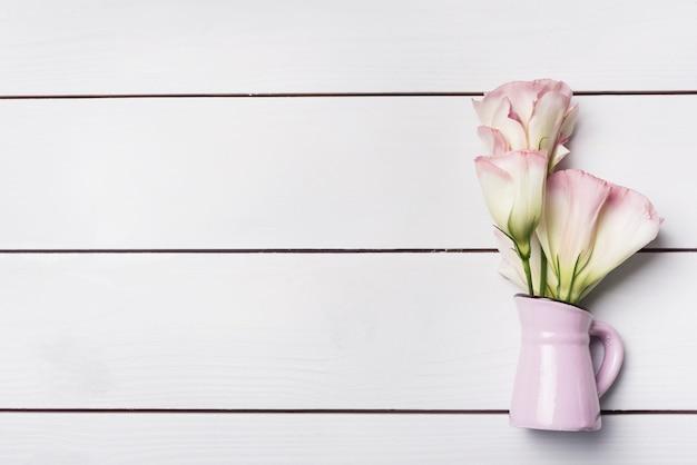 L'eustoma fiorisce nel vaso rosa sopra il fondo di legno della plancia