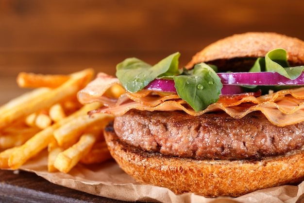 L'hamburger e le patate fritte si chiudono su su fondo di legno.